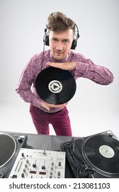 Half-length portrait of excited young DJ with stylish haircut with headphone by turntable posing with vinyl record isolated on white background