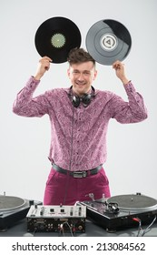Half-length portrait of excited young DJ with stylish haircut, bow tie having fun with vinyl record showing Mickey Mouse ears isolated on white background