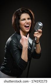 Half-length portrait of female rock singer wearing black jacket and keeping mic on grey background. Concept of music and rave