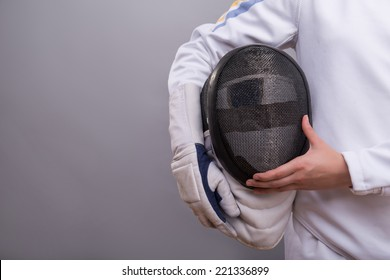Half-length portrait of the girl wearing white fencing costume holding the fencing mask. Isolated on grey background