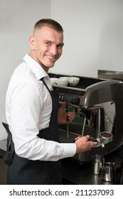 Half-length portrait of handsome young smiling barista making coffee for us using coffee machine