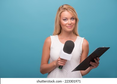 Half-length portrait of lovely fair-haired TV presenter wearing pretty white dress standing to us holding a microphone holding a folder. Isolated on blue background
