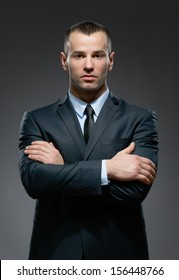 Half-length portrait of man wearing business suit and black tie with crossed arms