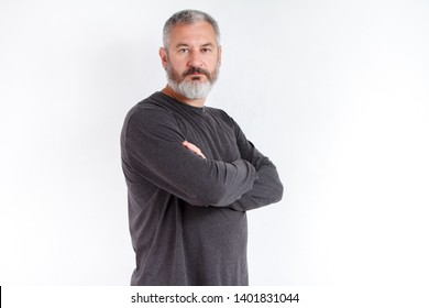 Half-length portrait of a serious gray-haired bearded man in a gray t-shirt on a white background.