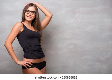 Half-length portrait of sexy smiling dark -haired young woman in nice eyeglasses wearing black vest and shorts standing aside showing her perfect figure
