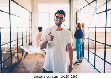 Half-length portrait of skilled team member showing finger up ok gesture working on successful project in office, handsome guy satisfied with super work looking at camera with colleagues on background