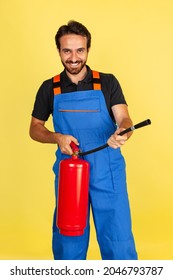 Half-length portrait of smiling young bearded man, male auto mechanic or fitter wearing blue work dungarees isolated over yellow studio background. Concept of funny meme emotions, ad, job