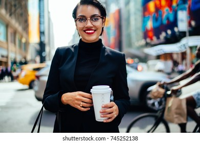 Half-length portrait of successful female entrepreneur looking standing on urban background with coffee go, smiling businesswoman in elegant wear looking at camera strolling on new york street