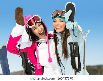 Half-length portrait of two female skier friends with hands up