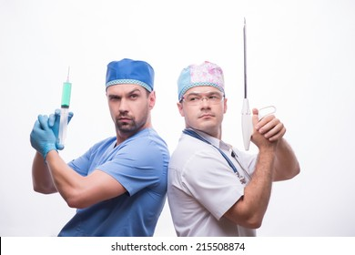 Half-length portrait of two funny doctors wearing medical dress standing back to each other holding injector and medical apparatus like weapon. Isolated on white background