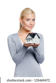 Half-length portrait of woman in grey pullover with small model house, isolated on white