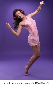 Half-length portrait of wonderful young woman with curly hair wearing nice pink dress dancing like a princess. Isolated on blue background
