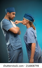 Half-length portrait of young fair-haired angry nurse wearing blue medical dress chiding the doctor holding black cardboard for copy place. Isolated on blue background