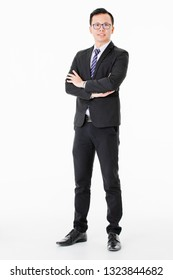 Half-length portrait of young handsome Asian man wearing eyeglasses in business suit proudly standing talking on smartphone and look at camera on isolated white background