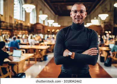 Half-length portrait of young prosperous male professor in eyeglasses spending time in public library, handsome successful writer looking at camera standing with crossed arms posing in reading hall