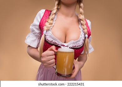 Half-length portrait of young sexy blonde with big breast wearing pink dirndl with white blouse holding the beer mug Isolated on dark background