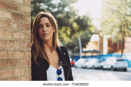 Half-length portrait of young stylish caucasian woman with long hair wearing leather jacket looking aside while standing on a street leaning on a brick wall. Pensive attractive female looking aside.