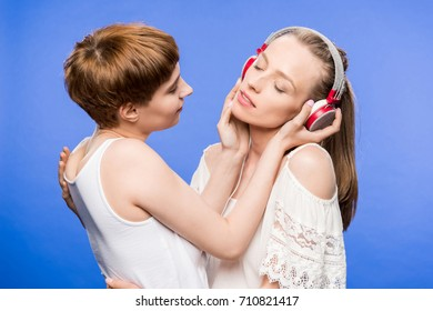 Half-length shot of lesbian couple hugging and listening to music in big headphones
