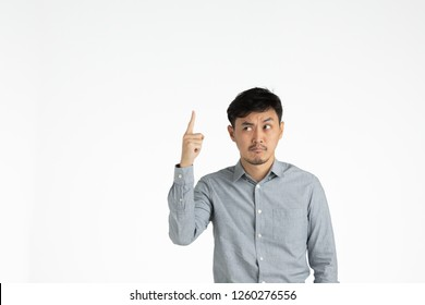 Half-length studio portrait of young,black hair Asian man in gray shirt, right index finger point up, perplexed,annoyed face, looking away from camera on isolated white background