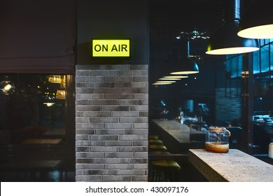 Half-lighted room in a mexican restaurant. There is a brick wall with glowing signboard and windows. On the right there is a light rack with jar on it and glowing lamps over it. Other side of the room
