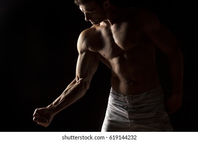 half-naked handsome and muscular young man posing on a black background