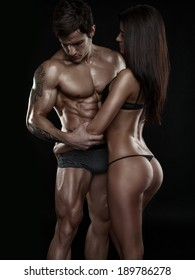 half-naked sexy couple, muscular man holding a beautiful woman isolated on a black background