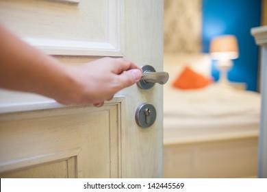 half-open door of a bedroom with hand