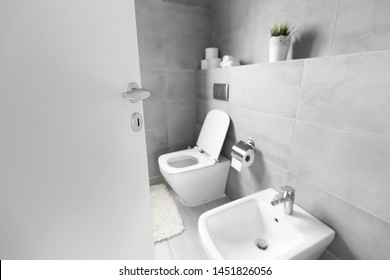 Half-open door to luxury bathroom with white ceramic bidet and toilet, nobody