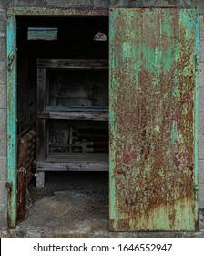 half-opened old metal door of the storehouse