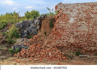 A half-ruined brick wall on the site of a former agricultural farm