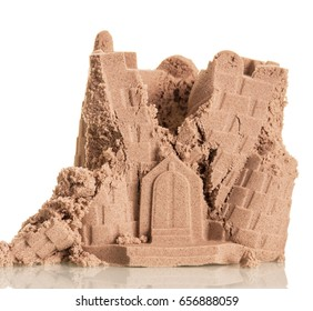 Half-ruined tower of sand isolated on a white background.