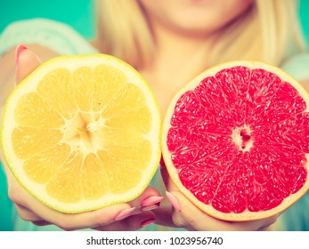 Halfs of yellow and red grapefruit citrus fruit in female hands closeup. Woman dietician recommend healthy diet nutrition.