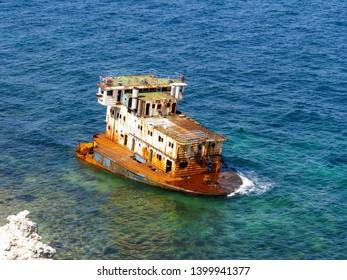Half-sunken ship at the shoreline.