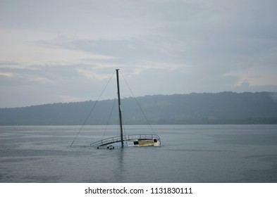 A half-sunken yacht is in a bay, its mast rising up into the overcast sky. Some children are swimming nearby. Tree-covered hills can just be seen through the mist.