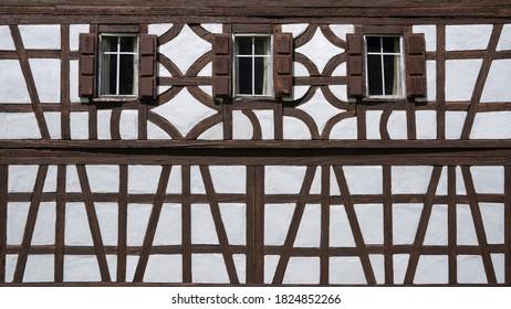 Halbholz-Fassade eines Modellbau-Hauses mit drei Fenstern, teilweise verwittert