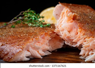A half-torn piece of smoked salmon fillet on a wooden Board on a dark background