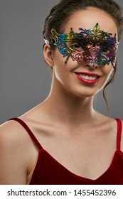 Half-turn portrait of smiling girl with tied back dark hair, wearing wine red crop top. The young lady is looking at camera, wearing iridescent carnival mask with fancy perforation and jutting edges.