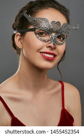 Half-turn portrait of smiling woman with dark hair, wearing wine red crop top. The young lady is tilting her head, wearing silver carnival mask with fancy perforation in view of heart in forehead.