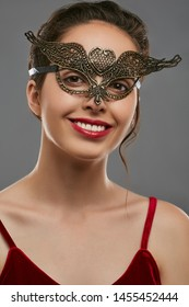 Half-turn portrait of smiling woman with dark hair, wearing wine red crop top. The young girl is tilting her head, wearing golden carnival mask with fancy perforation in view of heart in forehead.