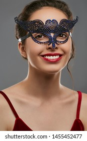 Half-turn portrait of smiling woman with dark hair, wearing wine red crop top. The young girl is looking at camera, wearing blue carnival mask with fancy perforation in view of heart in forehead.