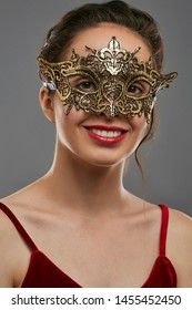Half-turn portrait of smiling woman with tied back dark hair, wearing wine red crop top. The young girl is looking at camera, wearing golden carnival mask with fancy perforation and jutting edges.