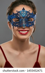 Half-turn portrait of smiling woman with tied back dark hair, wearing wine red crop top. The young girl is looking at the camera, wearing blue carnival mask with fancy perforation and jutting edges.