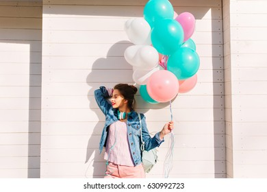 Half-turn portrait of stylish girl wearing denim jacket standing in front of white wooden wall. Gorgeous young brunette woman in pink clothes gladly posing with bunch of helium balloons looking away