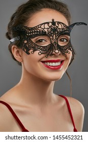 Half-turn shot of girl with dark hair, wearing wine red crop top. The smiling lady is looking at camera, wearing black masquerade mask with perforation and jutting edges. Vintage carnival accessory.