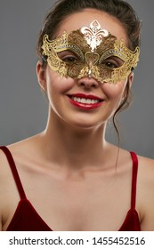 Half-turn shot of girl with dark hair, wearing wine red crop top. The smiling lady is looking at the camera, wearing golden Venetian carnival mask with fancy perforation. Vintage carnival accessory.