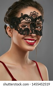 Half-turn shot of girl with dark hair, wearing wine red crop top. The smiling lady is looking at the camera, wearing black carnival mask with floral ornament perforation. Vintage carnival accessory.