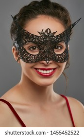 Half-turn shot of girl with dark hair, wearing wine red crop top. The smiling lady is looking at camera, wearing black masquerade mask with perforation and sharp edges. Vintage carnival accessory.