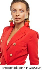 Half-turn shot of girl with tanned skin, wearing red blazer and long dangle earrings, adorned with massive metal pendants and bright red tassels. The woman with slicked down hair is looking to side.