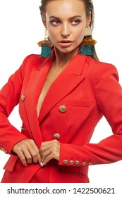 Half-turn shot of lady with tanned skin, wearing red blazer and long dangle earrings, adorned with massive metal pendants and emerald tassels. The woman with slicked down hair is looking to side.