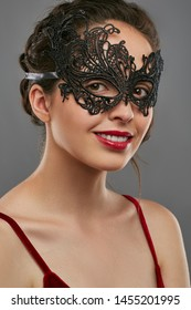Half-turn shot of smiling lady with tied back dark hair, wearing wine red crop top. The girl is looking at camera, wearing asymmetric black carnival mask with perforation, posing on gray background.